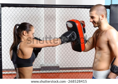 Sparring fight. Female mixed martial art fighter training with a couch in fighting cage