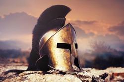 Spartan fiction helmet on rocks with sunset sky.