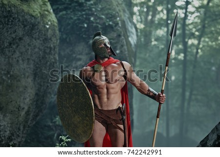 Spartan warrior in a battledress walking in the woods with his weapon.
