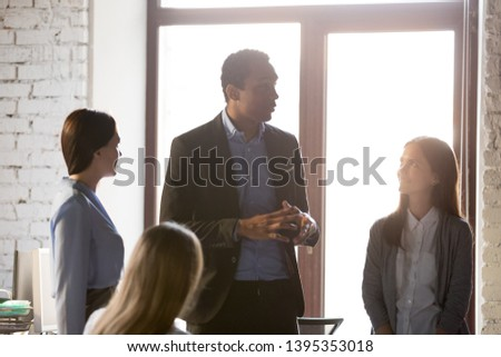 Speaker african team leader business coach giving instructions to employees present explain strategy company policy. Boss planning future projects with subordinates gather together at office workplace