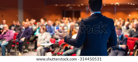 Speaker at Business Conference with Public Presentations. Audience at the conference hall. Entrepreneurship club. Rear view. Panoramic composition. Background blur.