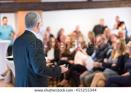 Speaker at Business Conference with Public Presentations. Audience at the conference hall. Entrepreneurship club. Rear view. Horisontal composition. Background blur. #455255344
