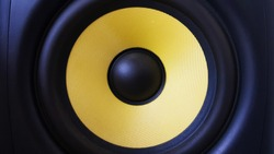Speaker background. Woofer, yellow subwoofer close-up. Professional studio equipment. Vocal monitor for mixing and recording music. High quality desk monitors