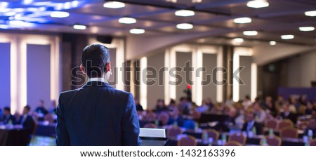 Speaker giving a talk at a corporate business conference. Audience in hall with presenter in front of presentation screen. Corporate executive giving speech during business and entrepreneur seminar. #1432163396