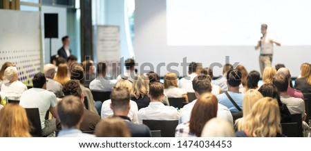 Speaker Giving a Talk at Business Meeting. Audience in the conference hall. Business and Entrepreneurship. Panoramic composition suitable for banners.