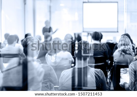 Speaker Giving a Talk at Business Meeting. Audience in the conference hall. Business and Entrepreneurship. Trough the glass door look.