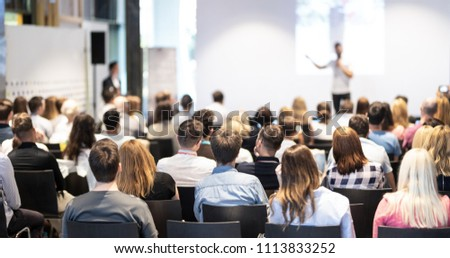 Speaker giving a talk in conference hall at business event. Audience at the conference hall. Business and Entrepreneurship concept. Focus on unrecognizable people in audience. #1113833252