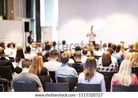 Speaker giving a talk in conference hall at business event. Audience at the conference hall. Business and Entrepreneurship concept. Focus on unrecognizable people in audience. #1115320727