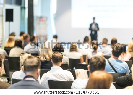Speaker giving a talk in conference hall at business event. Audience at the conference hall. Business and Entrepreneurship concept. Focus on unrecognizable people in audience. #1134779351