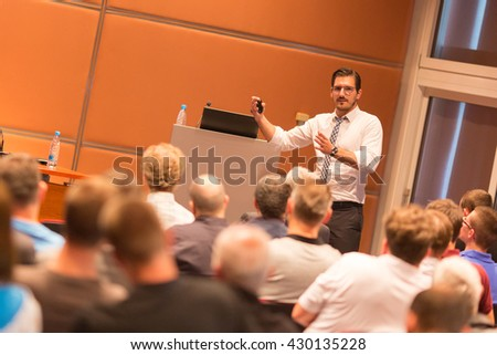 Speaker giving a talk in conference hall at business event. Audience at the conference hall. Business and Entrepreneurship.