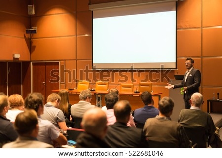 Speaker giving a talk in conference hall at business event. Audience at the conference hall. Business and Entrepreneurship concept. Copy space on white screen.