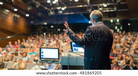 Shutterstock Speaker giving a talk on corporate Business Conference. Audience at the conference hall. Business and Entrepreneurship event.