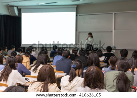 Speaker giving presentation in class of club at university in Japan.