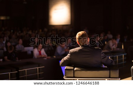 Speaker Giving Speech to Audience in Conference Hall Auditorium. Presenter Presenting Presentation to Audience. Defocused Blurred Conference Meeting People. Lecturer on Stage. Forum for Professionals