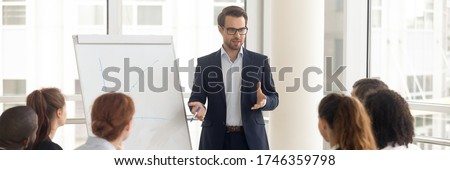 Speaker talking to audience makes presentation using flip chart interacts with group of staff employees, corporate seminar, training activity concept. Horizontal photo banner for website header design