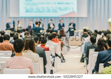 Speakers on the stage with Rear view of Audience in the conference hall or seminar meeting, business and education about investment concept