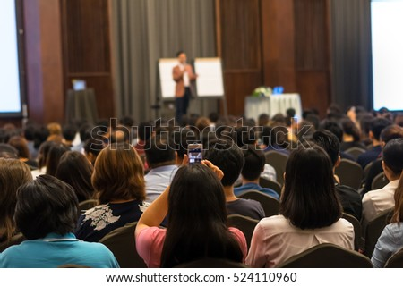 Speakers on the stage with Rear view of Audience in the conference hall or seminar meeting, business and education concept