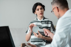 Speaking to doctor. Dark-haired businesswoman holding breast implant speaking to doctor