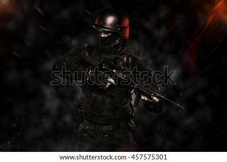 Spec ops police officer SWAT in black uniform and face mask Images