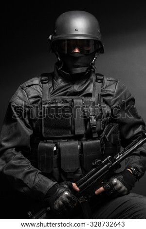 Spec ops police officer SWAT in black uniform studio Images and