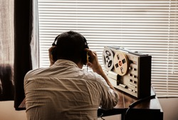 Special agent listens on the reel tape recorder. Officer wiretapping in headphones. KGB spying of conversations.
