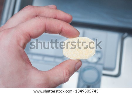 Special concentrated dishwashing tablet in hand #1349505743