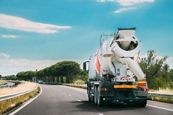 Special Concrete Transport Truck In-transit Mixer Unit In Motion On Country Road, Freeway. Freeway Motorway Highway. Business Drive Transportation And Development Concept. Concrete Truck Mixer