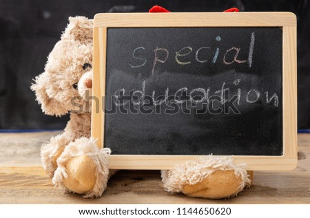 Special education. Teddy bear hiding behind a blackboard. Special education text drawing on the blackboard
