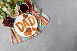Special Father's Day breakfast. Alphabet Pancakes with sprinkles, cherries and cup of tea on a gray concrete background with apple blossom branch. Top view, copy space