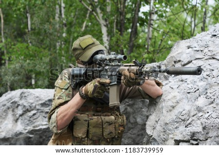 special forces soldier .assault rifle with silencer and optical sight.  behind cover waiting in ambush. #1183739959