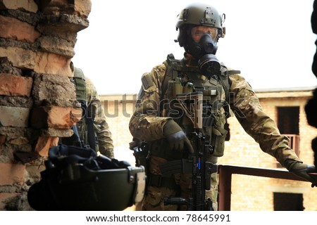 Special forces soldier during a black tactical exercises. Army Soldier  in full tactical gear with weapons  and gas mask. Real situation.