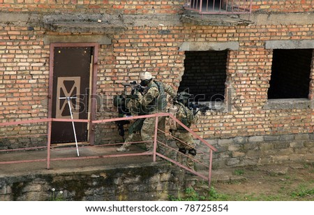 Special forces soldier during a black tactical exercises. Army Soldier  in full tactical gear with weapons  and gas mask. Intrusion inside the building after the detonation of an explosive.