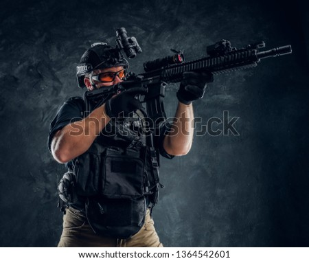 Special forces soldier holding an assault rifle with a laser sight and aims at the target. Studio photo against a dark textured wall