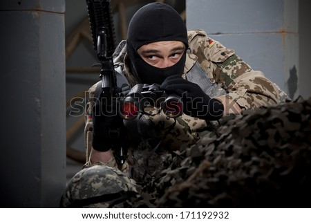 Special forces soldier with machine gun and binoculars hiding