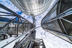 Special grain elevators for crop storage. Metal bridge from the roof of metal tank. View from below. Closeup.