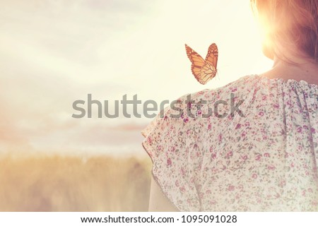 special moment of meeting between a butterfly and a girl in the middle of nature #1095091028