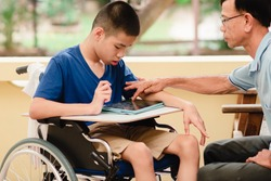 Special need child on wheelchair use a tablet in the house with his parent, Study or Work at home for safety from covid 19, Life in new normal education of special need kid,Happy disabled boy concept.
