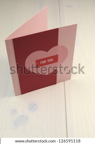 Special occasion Red and pink handmade gift card with heart and 'for you' message on natural white wooden table, for Valentine, Christmas, Easter, birthday, or Mothers Day.