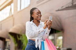 Special offer for regular customers. Laughing african american lady with colored shopping bags received message on phone, close up, copy space