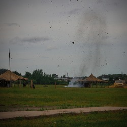 Special operation in a military camp, explosion. Lumps of earth are flying into the sky. On the territory of armed people. Green grass, forest. Vignetting.