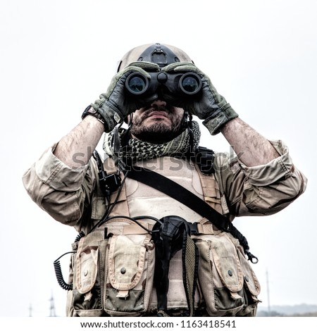 Special operations forces soldier, Navy SEAL scout in battle uniform and helmet, looking through binoculars, observing area, searching targets, monitoring enemy movements, directing artillery fire #1163418541