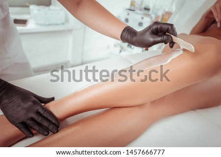 Special wax material. Attentive experienced cosmetologist working with wooden spatula while adding wax on the skin #1457666777