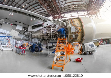 Specialist mechanic repairs the maintenance of a large engine of a passenger aircraft in a hangar. View of engine without bonnet, wing and landing gear