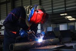 Specialist welder weld construction frame, welding spark , welder wearing full PPE to weld pipe