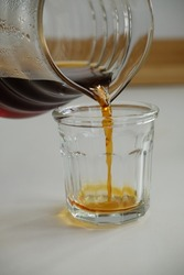 Specialty coffee concept. Black filter coffee pours into glass cup from glass decanter, close-up