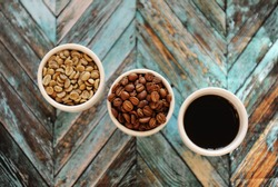 Specialty coffee concept. Green raw coffee beans, roasted coffee beans and black coffee in three white cups on turquoise wooden parquet background top view