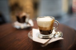Specialty coffees served on a wooden table in a bistro overlooking a shopping street