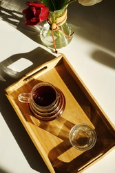 Specialty third wave coffee aesthetics. Freshly brewed pour over coffee served on a wooden bamboo tray on sunlit white table. Flowers in a coffee decanter