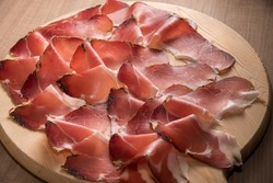 Speck, typical smoked ham from South Tyrol, Alto Adige in Italy - slices on wooden cutting board in top view