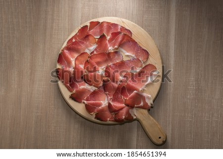 Photo of  Speck, typical smoked ham from South Tyrol, Alto Adige in Italy - slices on wooden cutting board in top view